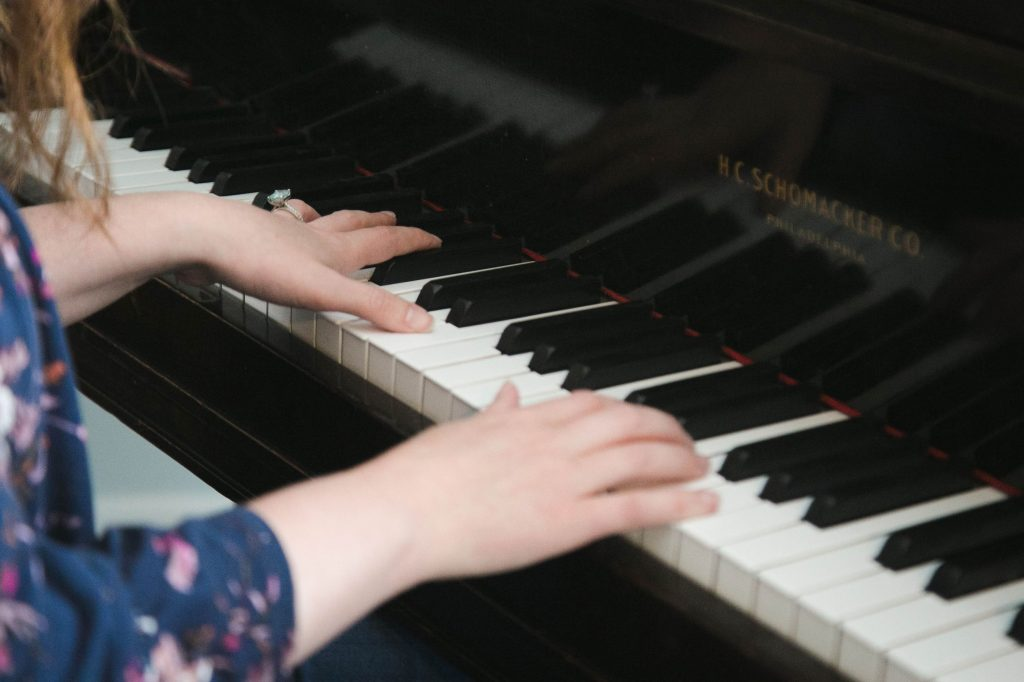 woman in floral shirt plays piano